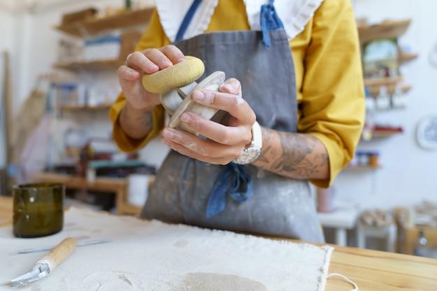 Artistiek hobby- en aardewerkstudio-eigendom vrouwelijk ambachtelijk werk met ruwe klei die mal in kan vormen