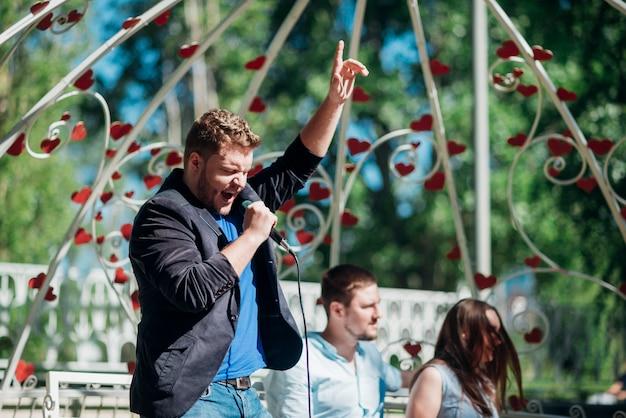 Artistiek mannelijk zingend lied in microfoon