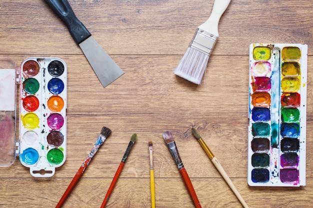 Artistieke eekhoornborstels, buizen van olieverf en waterverven op een houten achtergrond. het palet van vierentwintig kleuren. gebruikte hulpmiddelen voor kunstenaars en schoolkinderen. hulpmiddelen voor kunst. set van artistieke tools