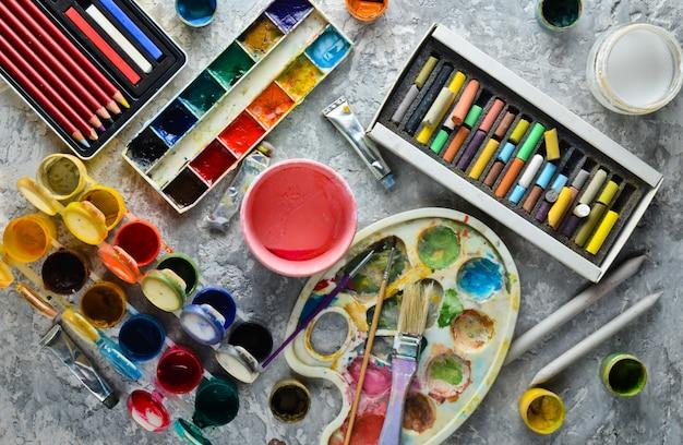 Artistieke hulpmiddelen voor het tekenen van schilderijen. palet, gouache, olieverf, penselen, kleurpotloden, pastel, kleurpotloden. bovenaanzicht.