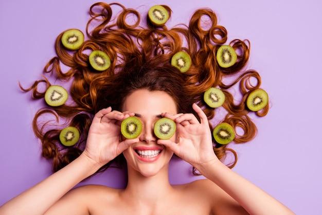 Artistieke roodharige vrouw poseren met kiwi in haar haar