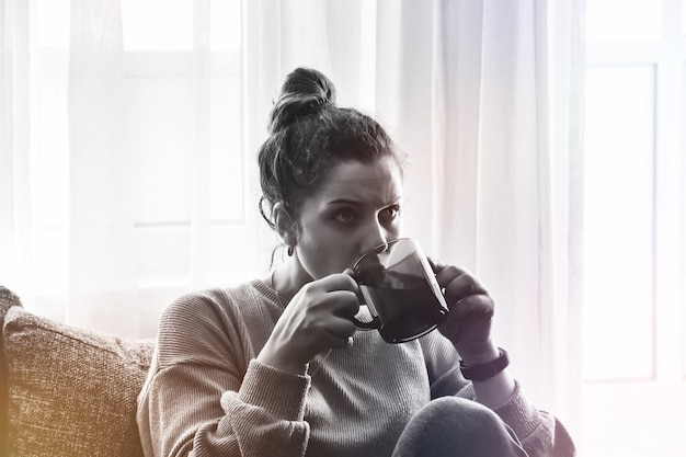 Artistieke ruisfilmkorrel. portret bang mooie blanke vrouw ontspannen drinken en wegkijken met warme koffie, thee. vrouwelijk gevoel geniet van het kijken naar films in vakantieochtendvakantie op de bank