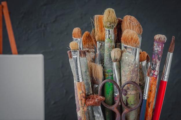 Artistieke uitrusting. de borstel en de brancard van de kunstenaar met een schoon canvas op de achtergrond van een grijze betonnen muur in de werkplaats.