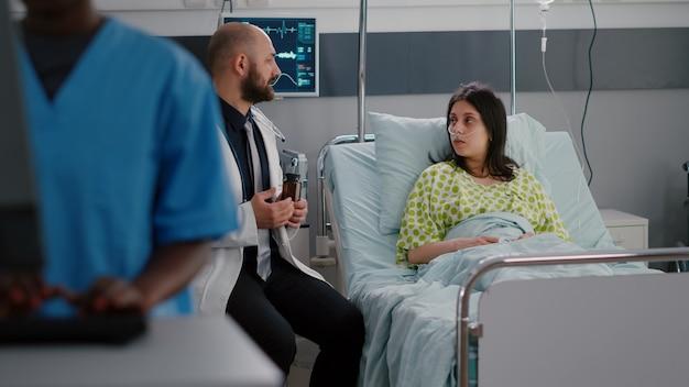 Arts arts die pilmedicatie uitlegt aan zieke vrouw tijdens farmaceutische afspraak in ziekenhuisafdeling. patiënt die in bed zit en vitaminerecept bespreekt die een gezondheidszorgbehandeling raadpleegt