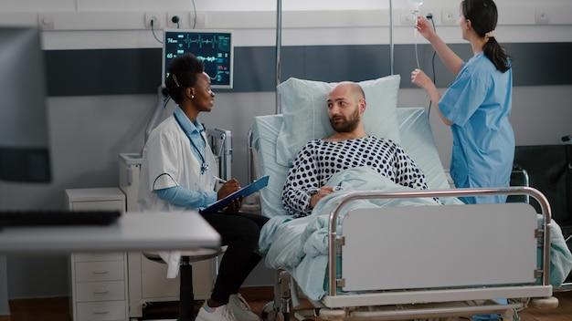 Arts arts die ziektebehandeling bespreekt die medisch symptoom op klembord schrijft