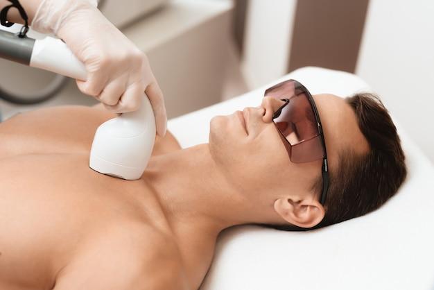 Arts behandelt zijn nek en gezicht met een speciaal apparaat