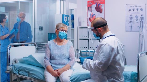 Arts bespreekt longdiagnose van gepensioneerde oude vrouw die op ziekenhuisbed zit in moderne privékliniek tijdens covid-19 pandemische gezondheidszorg wereldwijde crisis. dokter in beschermingsmiddelen van coro