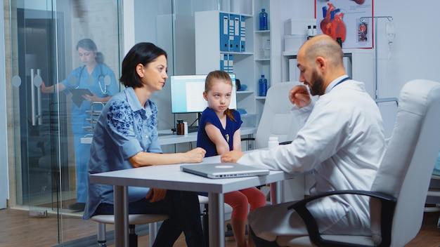 Arts bezig met diagnostisch onderzoek voor de gezondheid van kinderen, praten en schrijven. specialist in geneeskunde die gezondheidszorgdiensten verleent raadpleging diagnostisch onderzoek behandeling in ziekenhuiskast