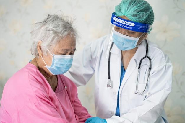 Arts controleert aziatische senior of oudere oude dame vrouw patiënt draagt ?? een gezichtsmasker in het ziekenhuis voor bescherming tegen infectie covid-19 coronavirus.