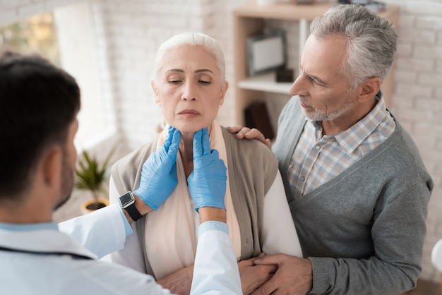 Arts controleert lymfeklieren van oudere vrouw.
