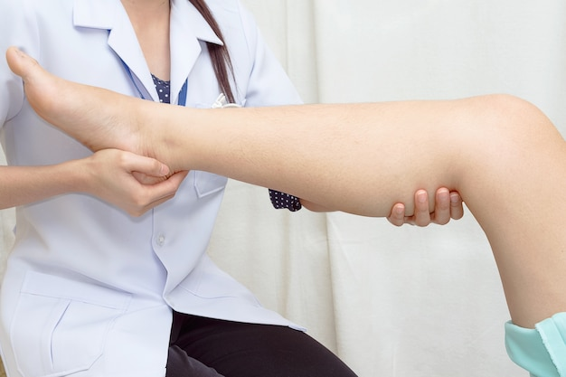 Arts de traumatoloog onderzoekt de knie van de patiënt