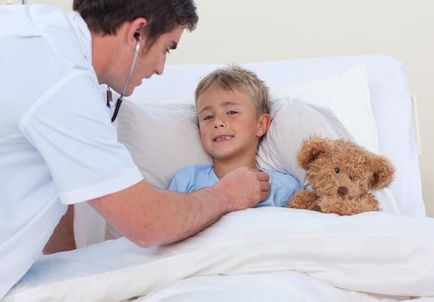 Arts die aan een kind luistert breaht met stethoscoop