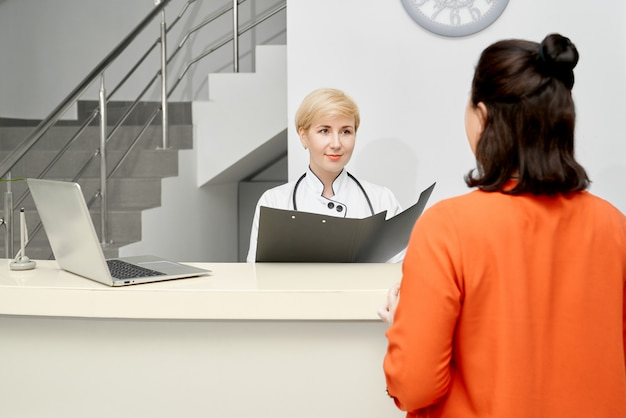 Arts die aan patiënt bij de receptie luistert.