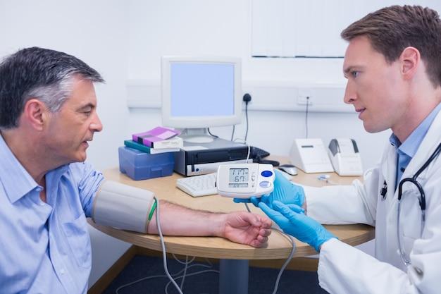 Arts die aan zijn patiënt over zijn bloeddruk spreekt