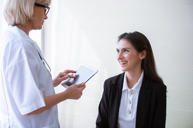 Arts die advies en het geduldige glimlachen geven die iets bespreken terwijl het zitten bij de lijst