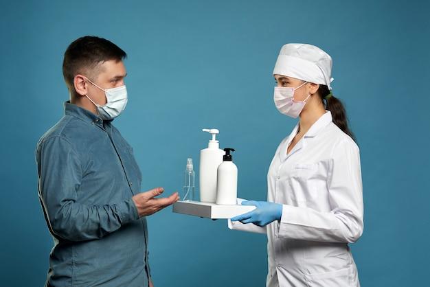 Arts die antibacteriële nevel op geduldige handen op blauwe muur toepast