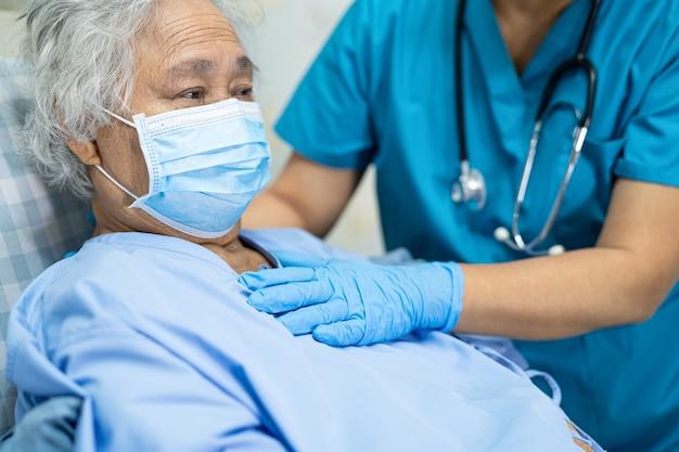 Arts die aziatische hogere vrouwenpatiënt controleert die een gezichtsmasker draagt ter bescherming van covid-19 coronavirus.