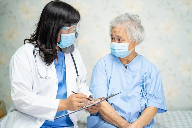 Arts die aziatische hogere vrouwenpatiënt controleert die een gezichtsmasker in het ziekenhuis draagt.