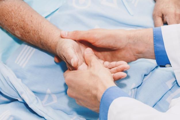 Arts die bejaardepersoonshand met zorg in het ziekenhuis houden gezondheidszorg en geneeskunde