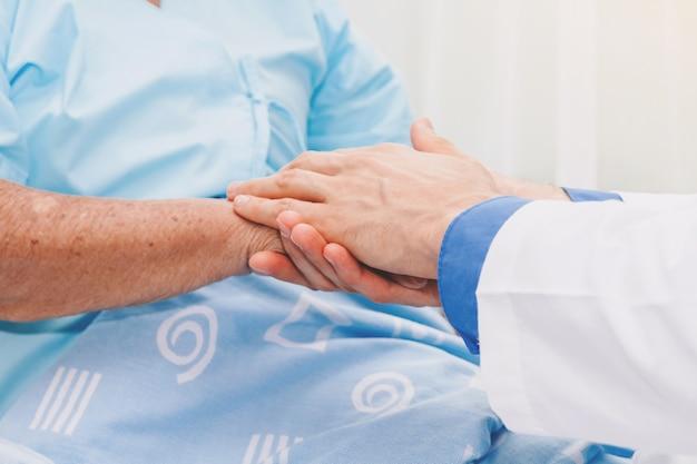 Arts die bejaardepersoonshand met zorg in het ziekenhuis houden gezondheidszorg en geneeskunde Premium Foto