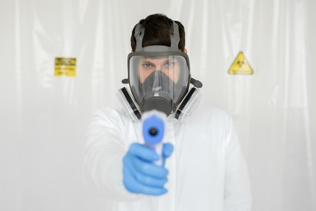 Arts die beschermend masker klaar om infraroodvoorhoofdthermometer te gebruiken draagt