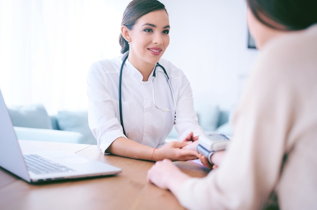 Arts die bloeddruk controleert aan patiënt in het ziekenhuis