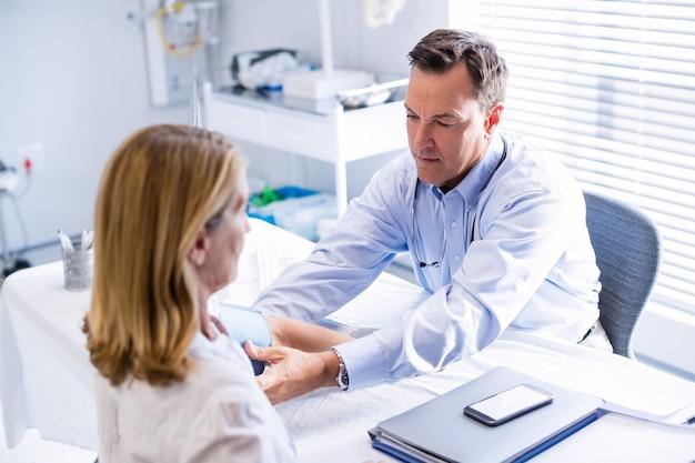 Arts die bloeddruk van een patiënt in kliniek controleert
