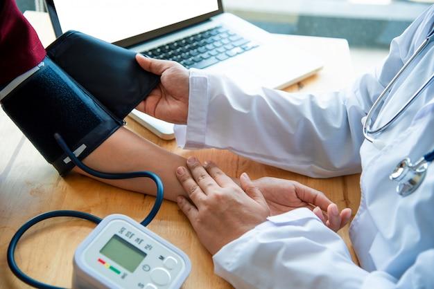 Arts die bloeddruk van haar patiënt meet