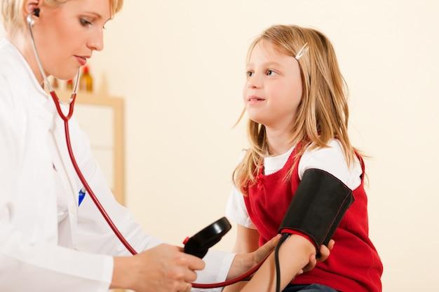 Arts die bloeddruk van kind meet