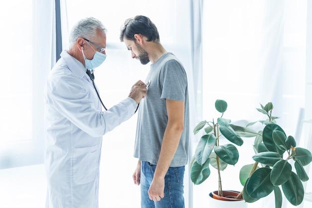 Arts die borst van patiënt onderzoekt