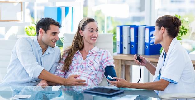 Arts die de bloeddruk van een zwangere patiënt met haar echtgenoot neemt