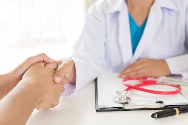 Arts die de hand van de patiënt houdt. geneeskunde en gezondheidszorgconcept