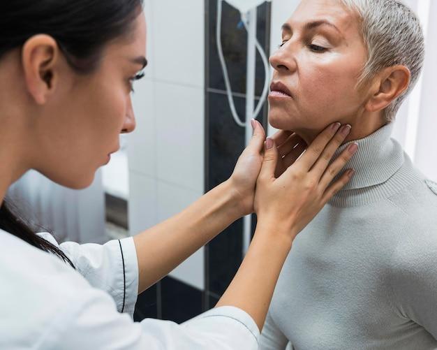 Arts die de nek van een patiënt controleert