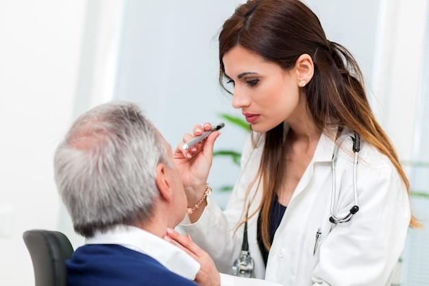 Arts die de ogen van de hogere mannelijke patiënt onderzoekt