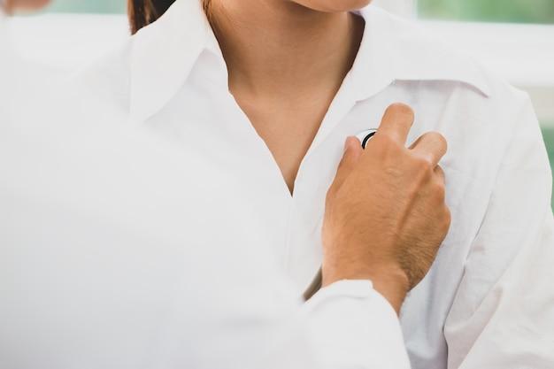 Arts die de patiënt van het hartlichaam controleert met een stethoscoop aziatische vrouw die ziek wordt met klembord op het bureau in het ziekenhuis. gezondheidszorg geneeskunde concept.