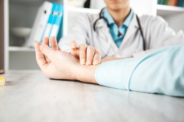 Arts die de pols van de patiënt in de kliniek neemt