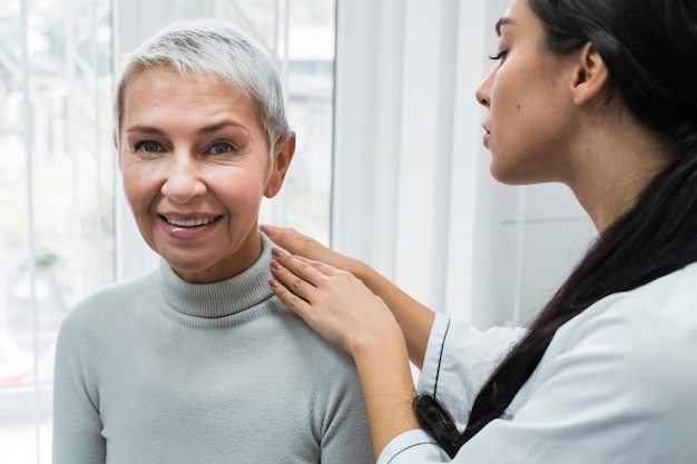 Arts die de schouder van een patiënt controleert