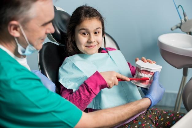 Arts die de tanden van het geduldige meisje behandelt bij tandartspraktijk