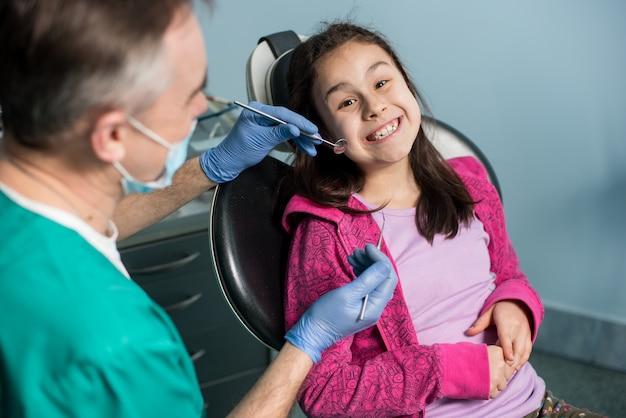 Arts die de tanden van het geduldige meisje bij tandartspraktijk behandelt