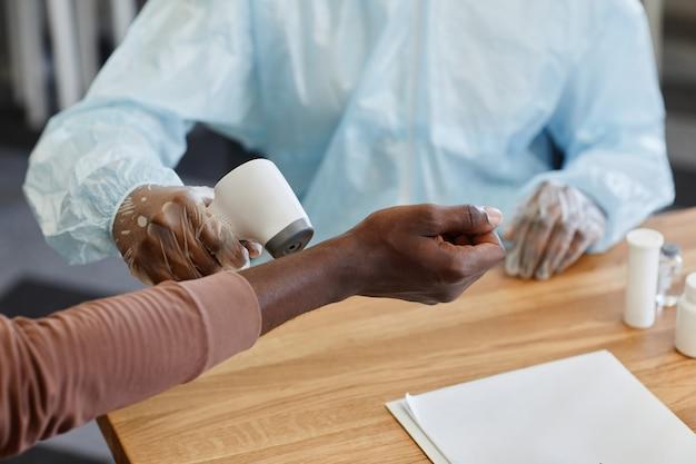 Arts die de temperatuur van de patiënt controleert