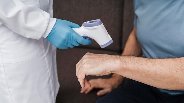 Arts die de temperatuur van de patiënt neemt