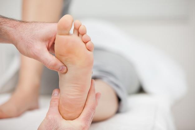 Arts die de voet van een vrouw houdt