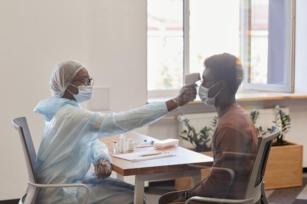 Arts die digitale contactloze infraroodthermometer gebruikt om de temperatuur van de patiënt te meten voordat hij...