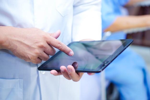 Arts die digitale tablet houdt en e-mail in de afdeling van het verpleeghuisziekenhuis leest.