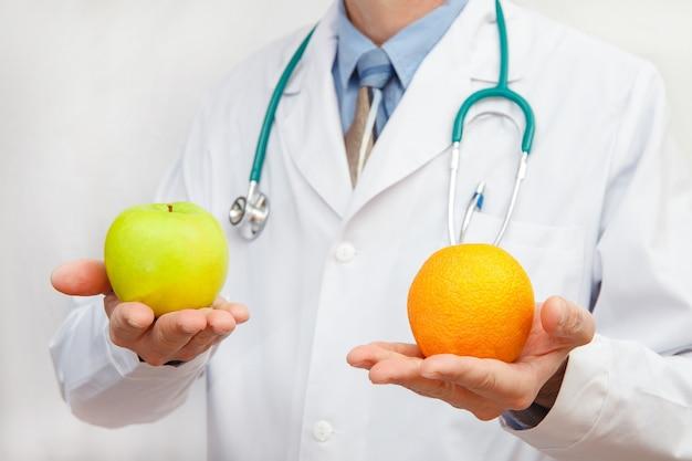 Arts die een appel en een sinaasappel houdt