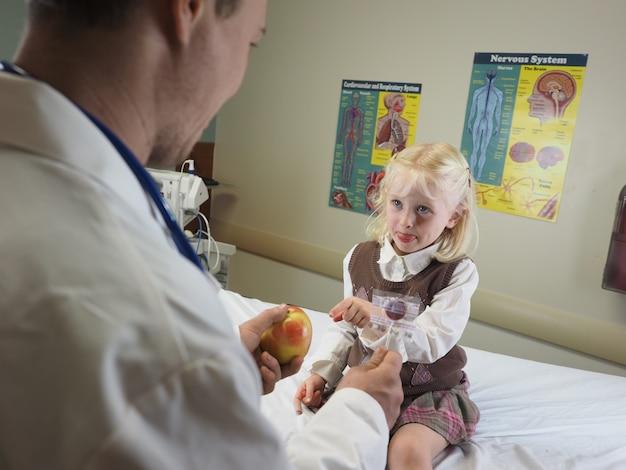 Arts die een appel geeft aan een klein meisje in een ziekenhuis