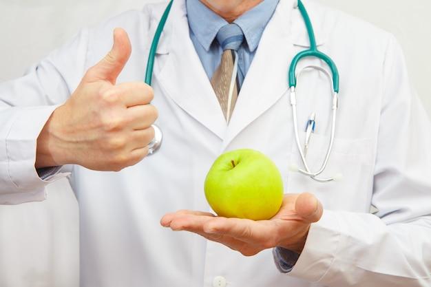 Arts die een appel houdt en duimen opgeeft