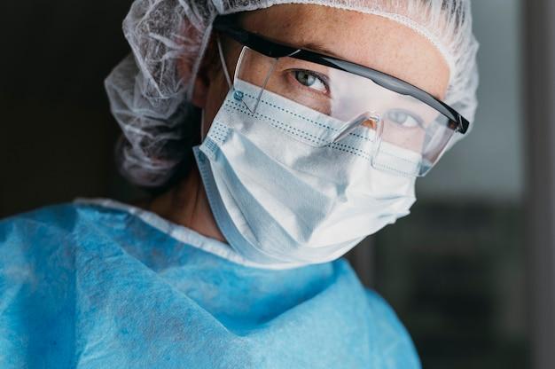 Arts die een gezichtsmasker en een veiligheidsbril draagt