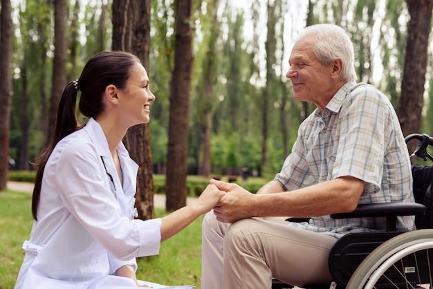 Arts die een glimlachende oude man hand houdt