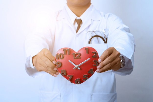 Arts die een klok, concept voor timing, medisch en gezondheidszorg houdt